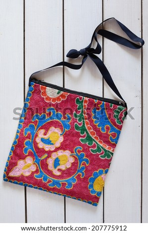 Handbag with suzani embroidery over white wooden background