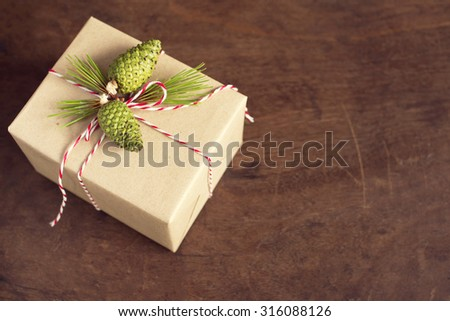 handcraft gift boxes gift box with pinecone and pine branch over wooden background.    - stock photo