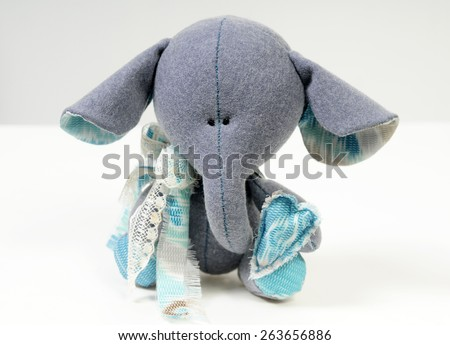 handcrafted sad beautiful baby elephant made of natural materials decorated with cotton and vintage lace  isolated on white - stock photo