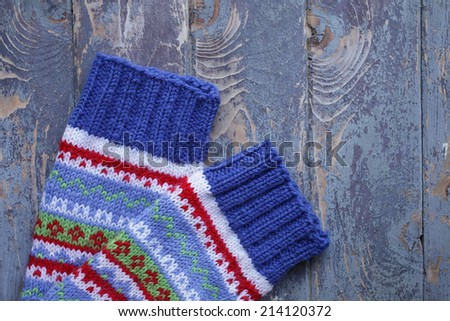 Handcrafted woolen socks on old wooden background - stock photo