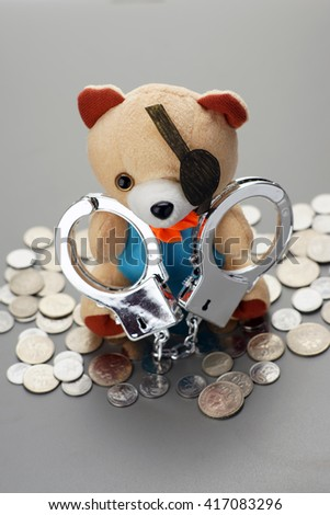 handcuff bad teddy bear with coins. criminal concept  - stock photo