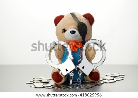 handcuff teddy bear with money. Crime concept - stock photo