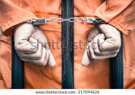 Handcuffed hands of a prisoner behind the bars of a prison with orange clothes - Crispy desaturated dramatic filtered look - stock photo