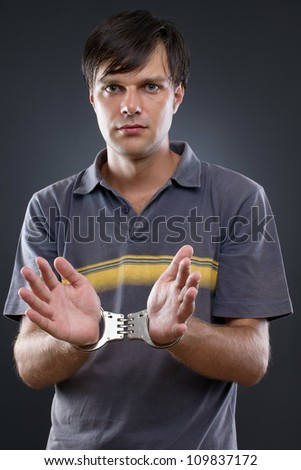 handcuffed man on gray backing - stock photo