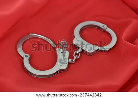 handcuffed on red silk fabric. Symbol of desire.  - stock photo