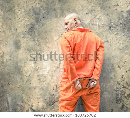 Handcuffed Prisoner in Jail waiting for Death Penalty - Guantanamo orange clothes - Grunge dramatic wall background - stock photo