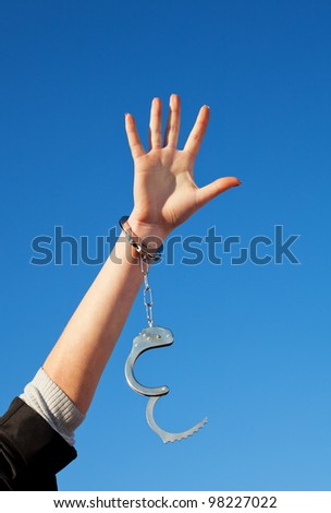 Handcuffed woman's hand against blue sky - stock photo