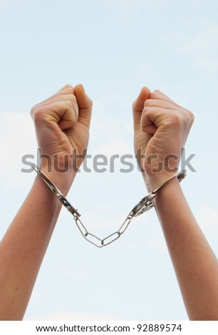 Handcuffed woman's hands against blue sky