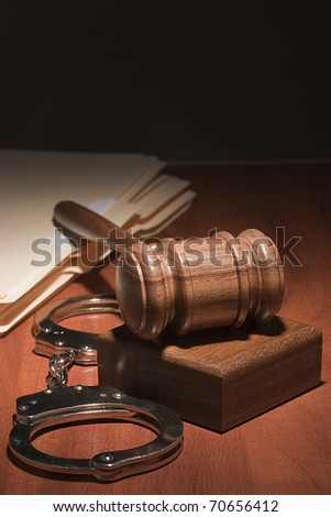 Handcuffs and a wooden gavel in front of manila folders. - stock photo
