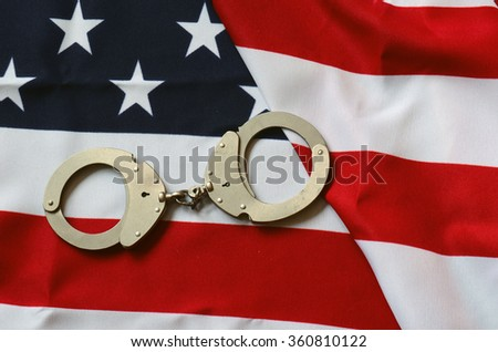 Handcuffs and American Flag - stock photo