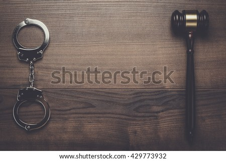 handcuffs and judge gavel on brown wooden background - stock photo
