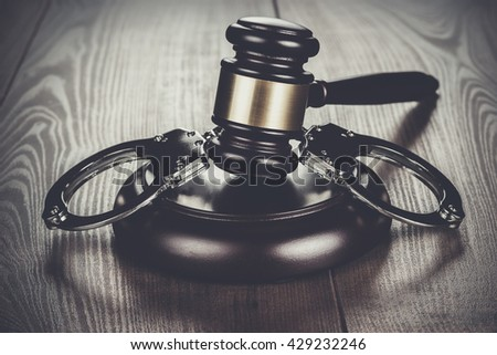 handcuffs and judge gavel on the brown wooden table - stock photo