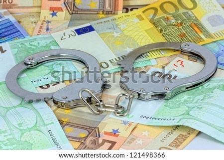 Handcuffs and money - stock photo
