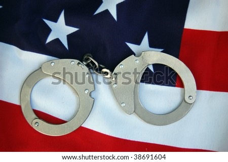 Handcuffs and USA flag - stock photo