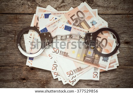 Handcuffs on euro banknotes, corruption or bribery concept - stock photo