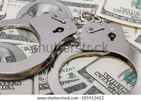 Handcuffs on money close up - stock photo
