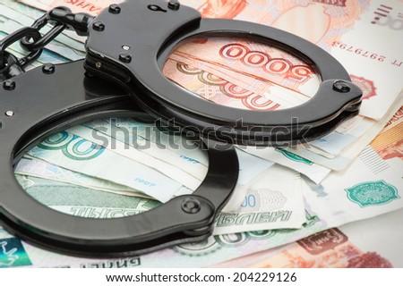 Handcuffs on Russian money - stock photo