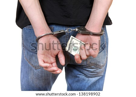 Handcuffs on the Hands with a Money Closeup Isolated on the White Background - stock photo