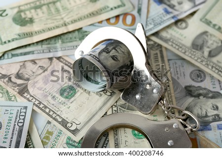 Handcuffs with rolled dollar banknote on paper background. Corruption concept - stock photo