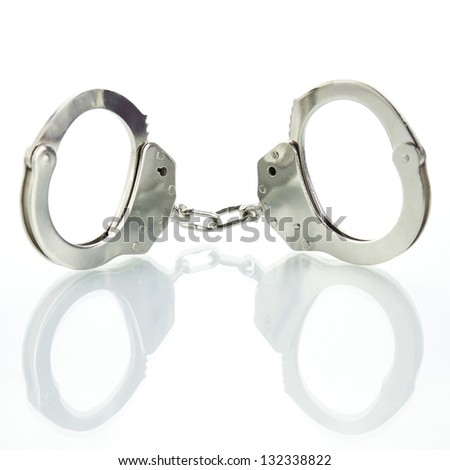 Handcuffs with shadow on a white background - stock photo
