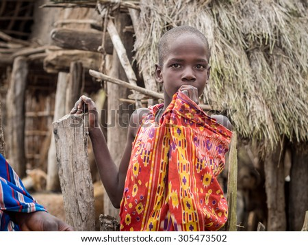 HANDENI, TANZANIA - AUGUST 01, 2015: Maasai boy in traditional outfit in his boma (village) in Tanzania, Africa.