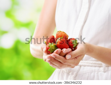 Handful of fresh ripe red juicy strawberries in hands of young woman in white dress on nature background. Healthy eco sweet food rich in vitamins. Product of organic farming.