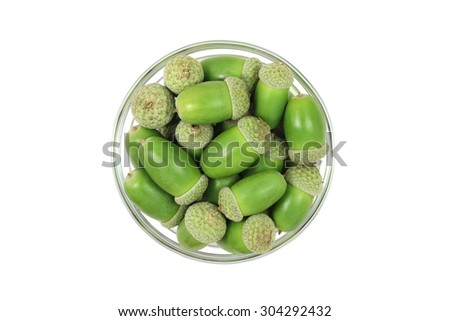 handful of green acorns in a glass cup on a white background - stock photo