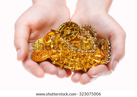 Handful of pirates coins in palm hands isolated on white - stock photo