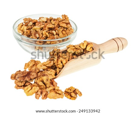 Handful of walnuts in scoop and glass bowl isolated on white background. Closeup. Selective focus. - stock photo