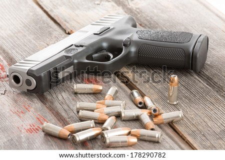 Handgun and a pile of scattered bullets lying on an old rustic wooden table conceptual of crime, violence, killing, coercion and protection of assets - stock photo