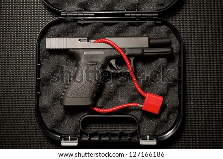 Handgun in Case With Cable Lock - stock photo