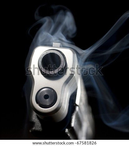 Handgun in the dark that has just gone off and is smoking