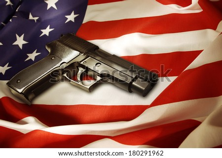 Handgun lying on American flag - stock photo
