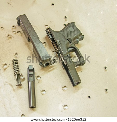 Handgun that has been broken down to its seperate parts - stock photo