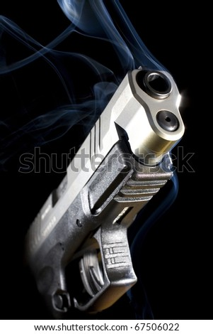 Handgun that has been shot so much smoke is pouring out - stock photo