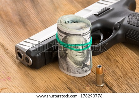 Handgun with a roll of 100 dollar bills and a single bullet lying on a wooden surface with the barrel and muzzle towards the camera conceptual of crime, a payoff, gun for hire or protection - stock photo