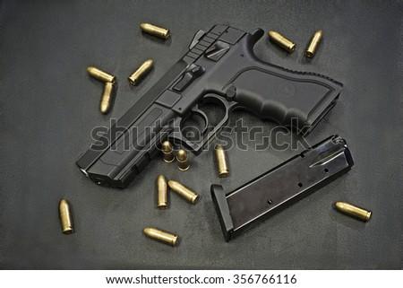 handgun with ammunition on a black surface - stock photo