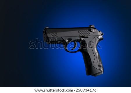 Handgun with blue and black background - stock photo