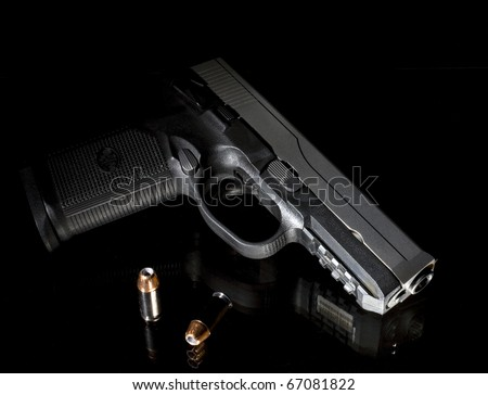 handgun with bullets that is on black glass - stock photo