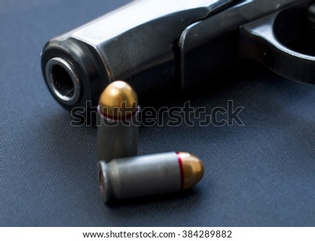handgun with cartridge on the black background
