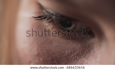 handheld closeup shot of teen girl eyes looking at smartphone screen in sunset light near window
