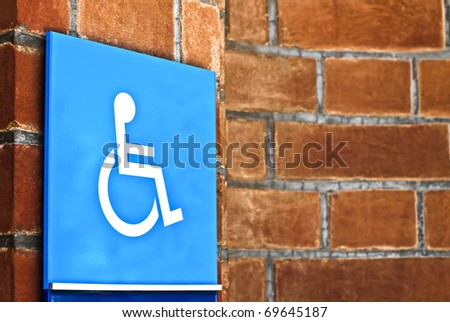 Handicap access sign on red brick wall - stock photo