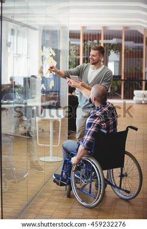 Handicap businessman assisting colleague while sticking adhesive notes on glass window in creative office
