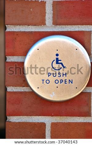 Handicap push button on brick - stock photo
