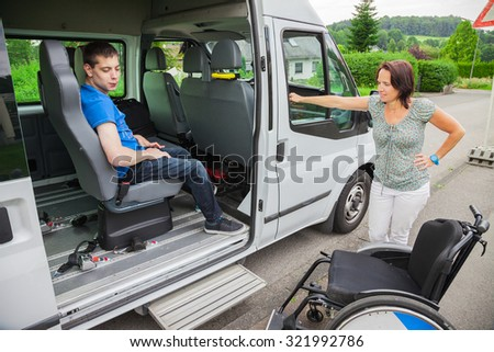 Handicapped boy is picked up by school bus - stock photo