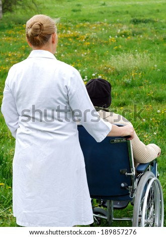 Handicapped elderly woman sitting in a wheelchair outdoor - stock photo