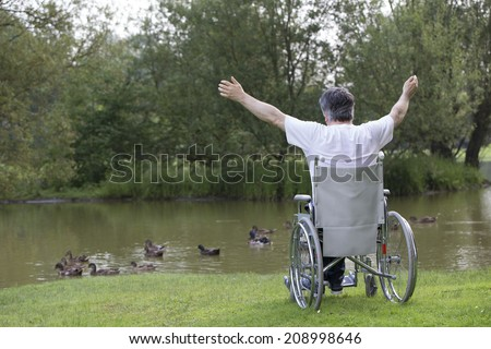 handicapped man on a wheelchair alone in a park - stock photo