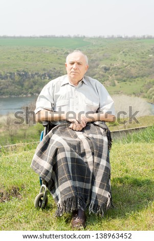 Handicapped man sitting in his wheelchair with a blanket over his legs enjoying the summer sunshine in a quiet rural location with scenic views