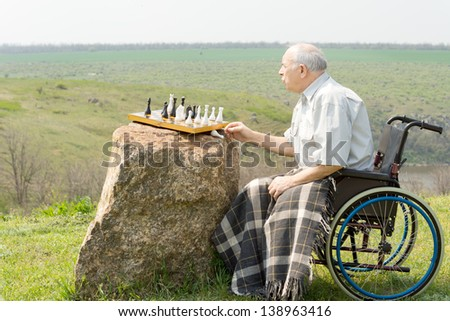 Handicapped pensioner playing chess outdoors sitting in his wheelchair with a rug over his knees and the chessboard balanced on a rock - stock photo
