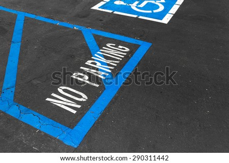 Handicapped reserved parking area with no parking white painted letters and blue diagonal lines on black asphalt. Rough cracked pavement. Wheelchair symbol in background. Room for text.  - stock photo